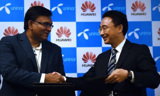 2015年,首席營運官Uninor Tanveer Mohammad 在簽署協議以實現印度整個電信網絡現代化後,與華為副總裁周鑫(Baker Zhou)握手。相片:AFP