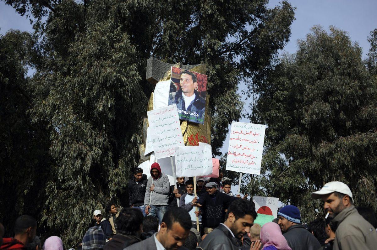 متظاهرون يلتفون حول صورة لرمز المظاهرات التونسية محمد بوعزيزي في 20 يناير/كانون الثاني 2011 في سيدي بوزيد. صورة: FRED DUFOUR / AFP AFP PHOTO / FRED DUFOUR (Photo by FRED DUFOUR / AFP)