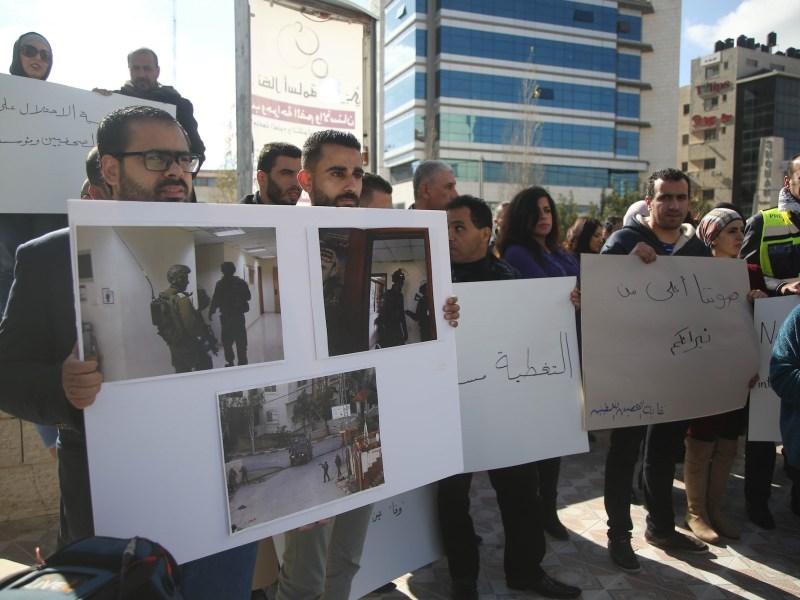 متظاهرون فلسطينيون ينددون باقتحام قوات إسرائيلية للمكتب الرئيس لوكالة أنباء وفا الفلسطينية في رام الله، الضفة الغربية في 11 ديسمبر، كانون   الأول 2018.   صورة: Issam Rimawi/الأناضول