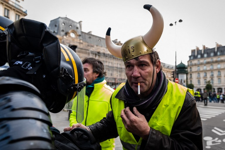 Police officer searches an anti-Macron demonstrator in Paris over the weekend. Photo: AFP