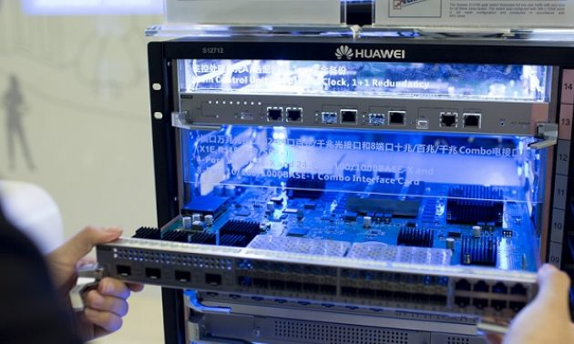 一名員工在華為FusionCube存儲系統中拿著介面卡。華為成功壟斷全球4G / 5G網絡設備。相片:Facebook