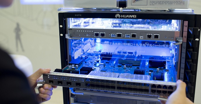 An employee holds an interface card in a Huawei FusionCube storage system. Huawei commands an effective monopoly of devices for the global 4G/5G networks. Photo: Facebook