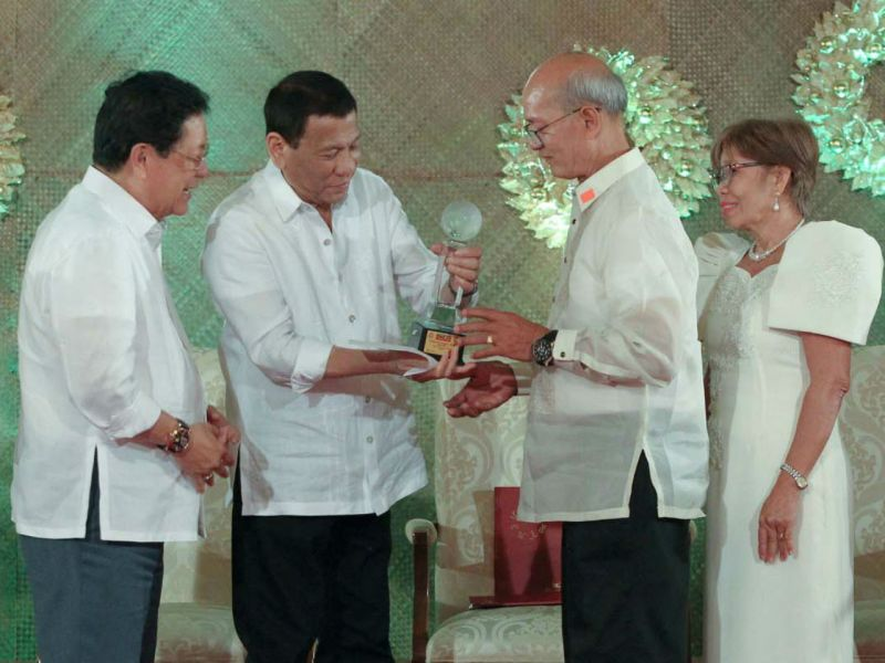 President Duterte gives an award to migrant worker Reynaldo Gaitan and his family for being the Model OFW Family of the Year. Photo: Philippine Presidential Office