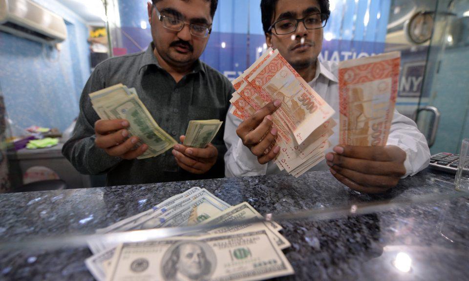 貨幣交易商在伊斯蘭堡的找換店數算巴基斯坦盧比和美元。相片:AFP/ Aamir Qureshi
