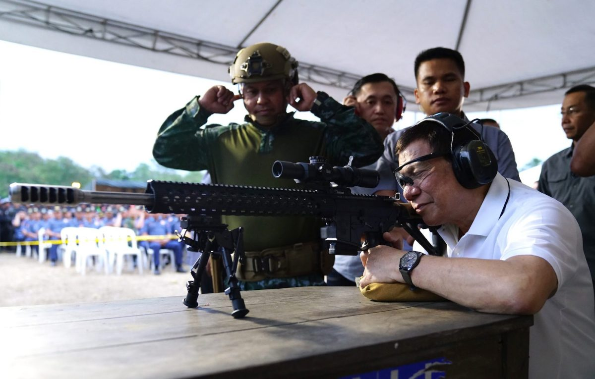 Philippine President Rodrigo Duterte fires a few rounds with a sniper rifle during the opening ceremony of the National Special Weapons and Tactics (SWAT) Challenge in Davao City in March 2018. Photo: AFP/Joel Dalumpines