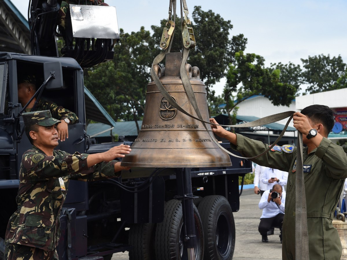 Philippine military personnel unload one of the three Balangiga church bells after it arrived from the US at a military airbase in Manila on December 11, 2018. Photo: AFP/Ted Aljibe