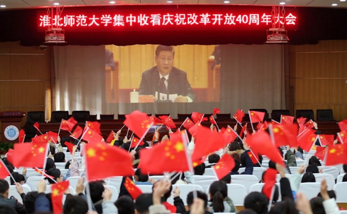 Local residents watch the live broadcast of President Xi Jinping's speech to celebrate the 40th anniversary of the country's reform policy. Photo: AFP