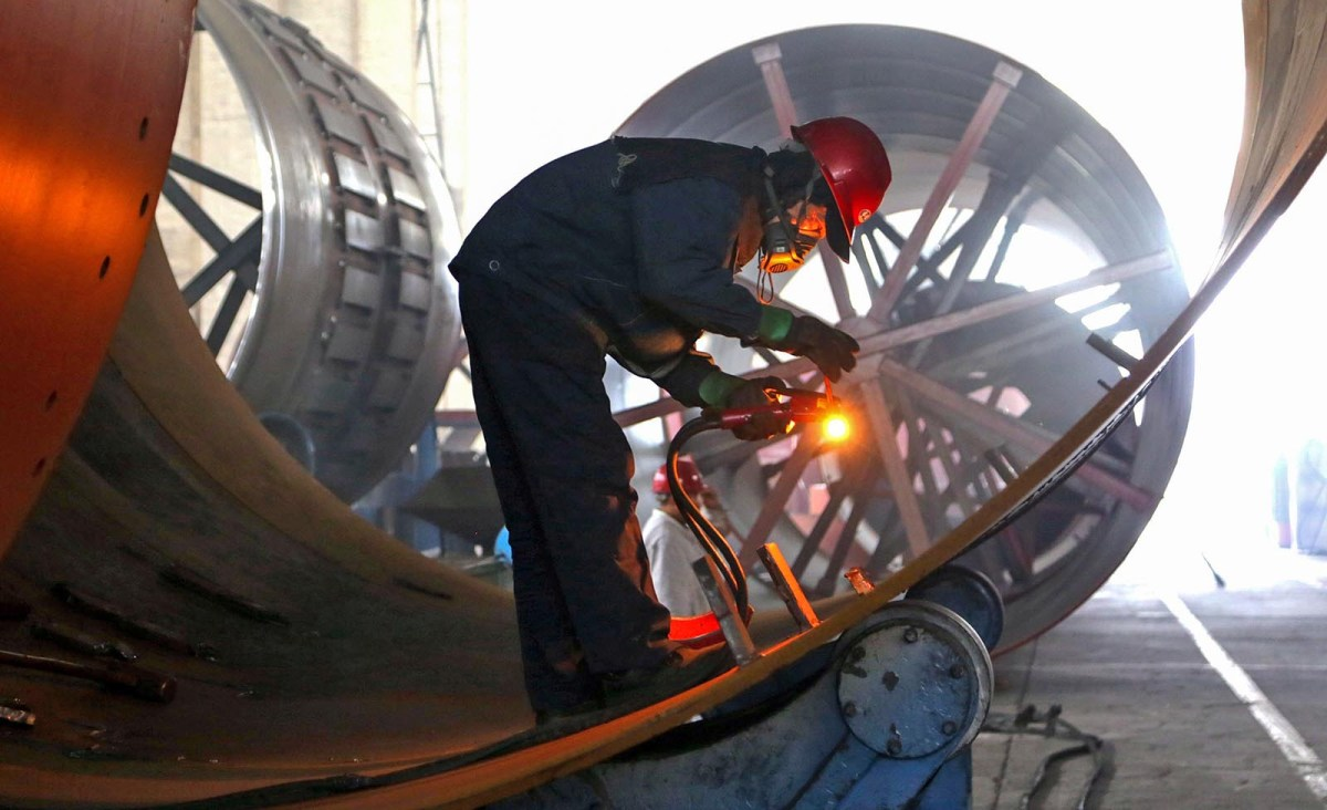 A welder works on rotary kiln at a factory in Haian in China's eastern Jiangsu province. Photo: AFP