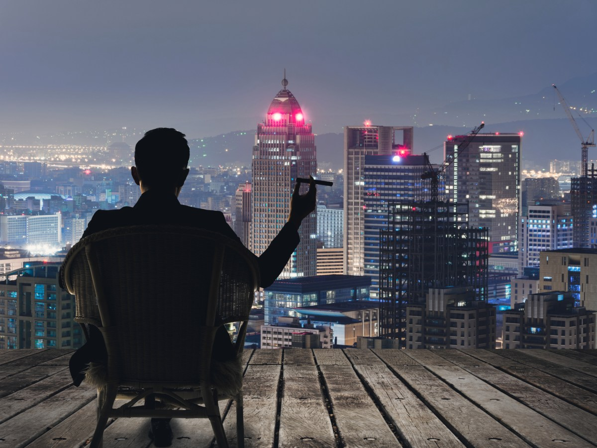 A businessman sits on a chair and holds a cigar while he looks over a city at night. Photo: iStock