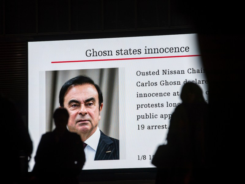 Pedestrians pass a TV screen showing a news program noting Carlos Ghosn's first day in court in Tokyo on January 8, 2019. The former Nissan boss said he had been 'wrongly accused and unfairly detained'. Photo: Behrouz Mehri / AFP