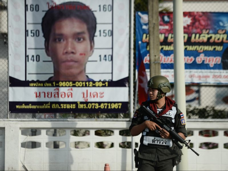 A Thai security force officer stands next to a banner of a suspect (back L) following a bomb attack at a civilian volunteer base by suspected separatists the night before in the Rangae district of Narathiwat province, December 29, 2018. Photo: AFP/Madaree Tohlala
