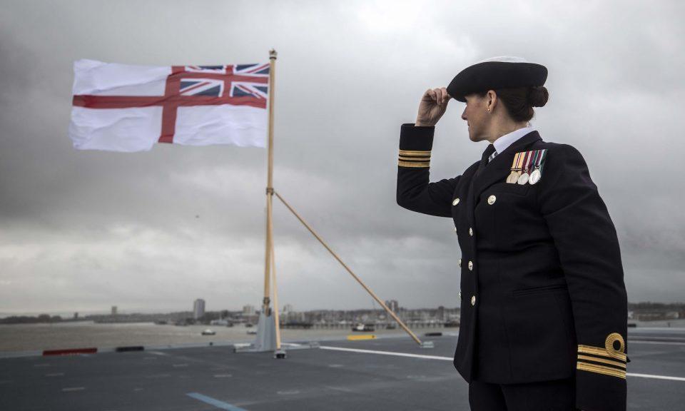 2017年12月7日,一名英國海軍軍官在「伊利沙伯女皇號」(HMS Queen Elizabeth)首次駛進位於英國南部樸茨茅夫的母港作「洗禮」儀式期間,抬頭看著船尾懸掛著的白色艦旗正在空中飄揚。相片:AFP / Richard Pohle