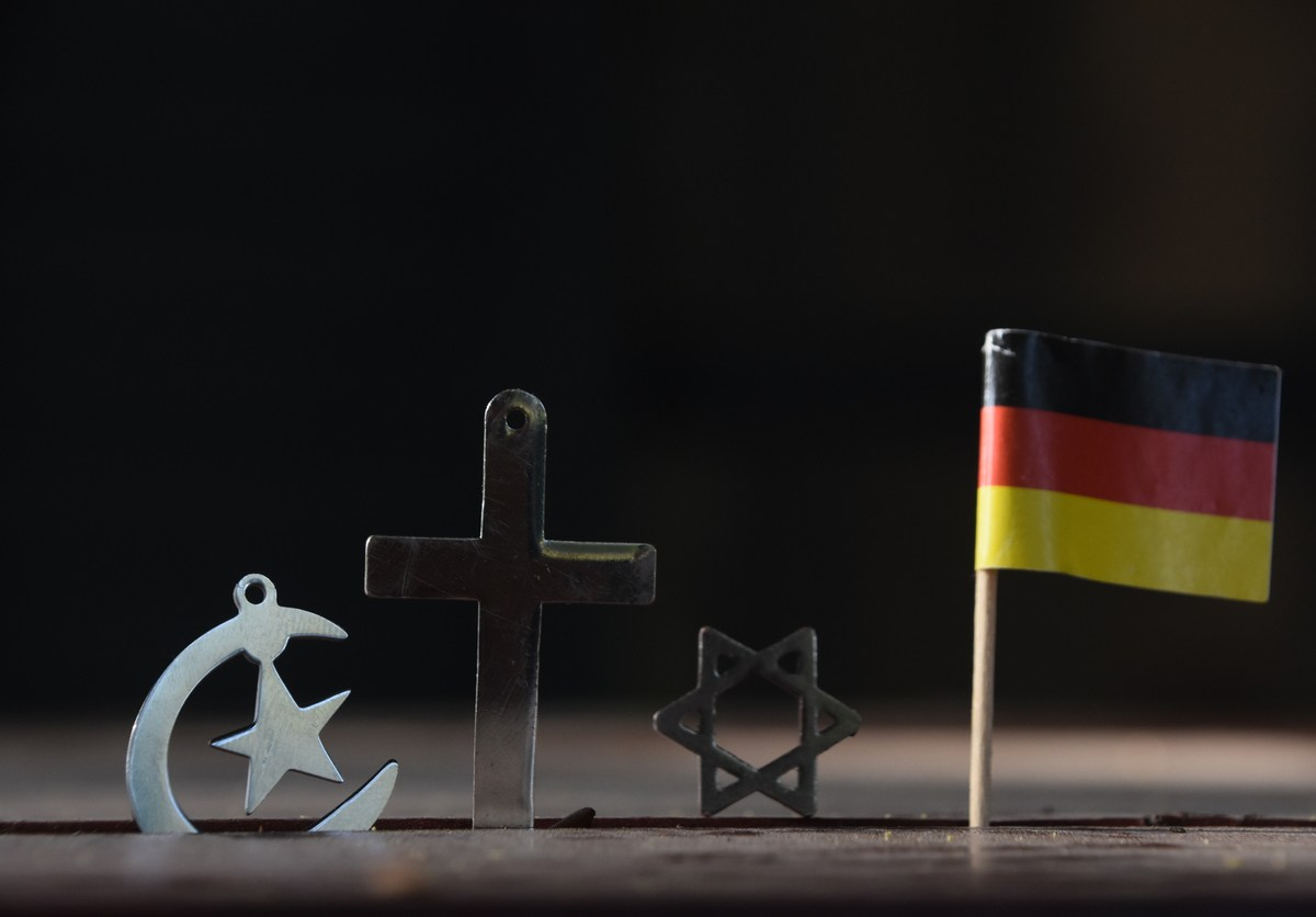 Symbols of the three religions - Judaism, Christianity and Islam With a German flag. Image: iStock