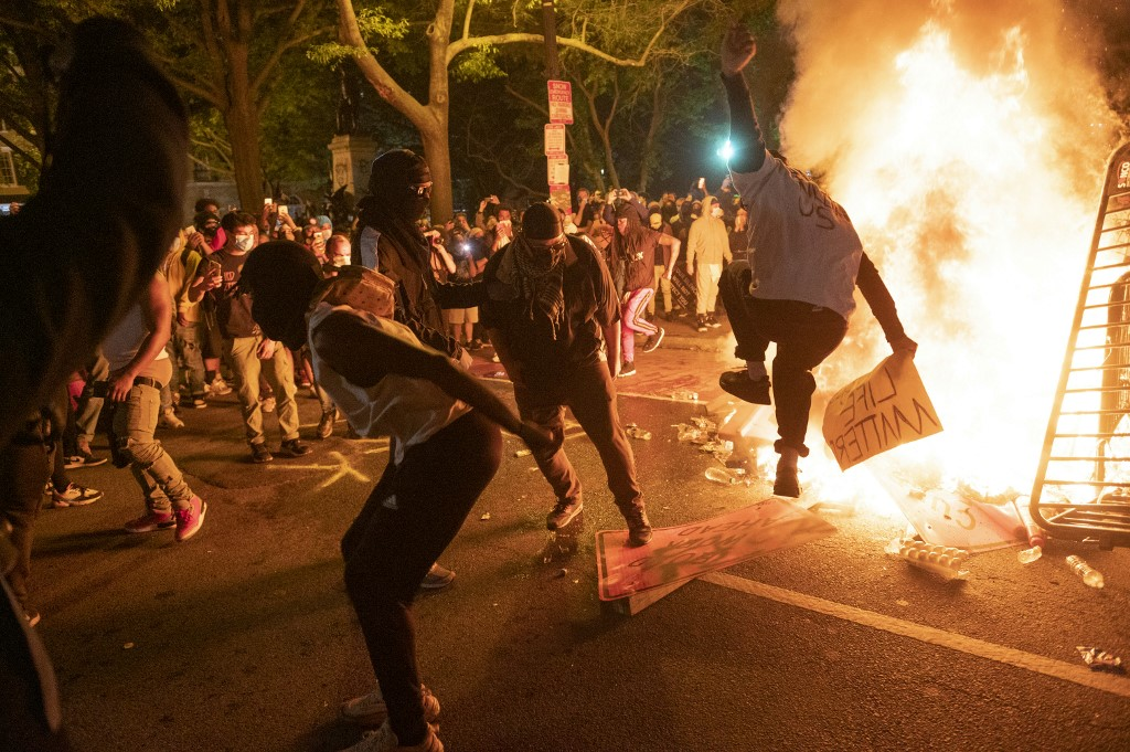 Protesters jump on a street sign near a burning barricade near the White House during a demonstration against the death of George Floyd on May 31, 2020 in Washington, DC. Photo: AFP