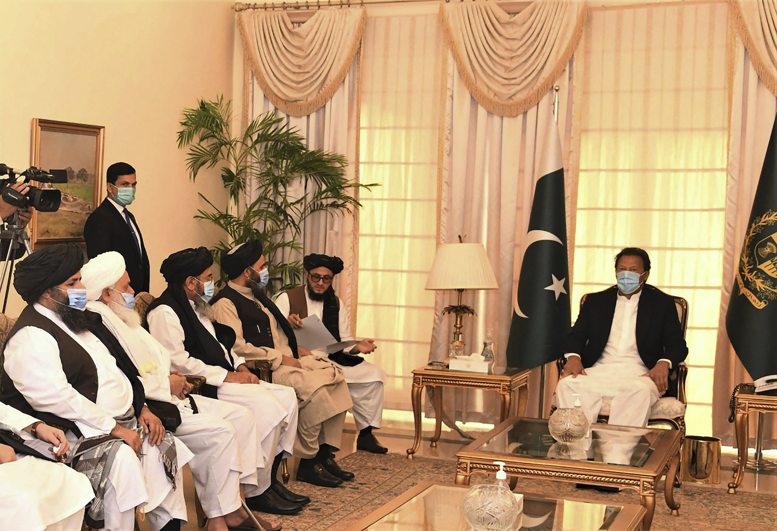 Pakistani Prime Minister Imran Khan (R) meets with Taliban co-founder Mullah Abdul Ghani Baradar (2d from the window on the left side of the picture) and his delegation in Islamabad on December 18, 2020. Photo: AFP / Pakistan Prime Minister Office