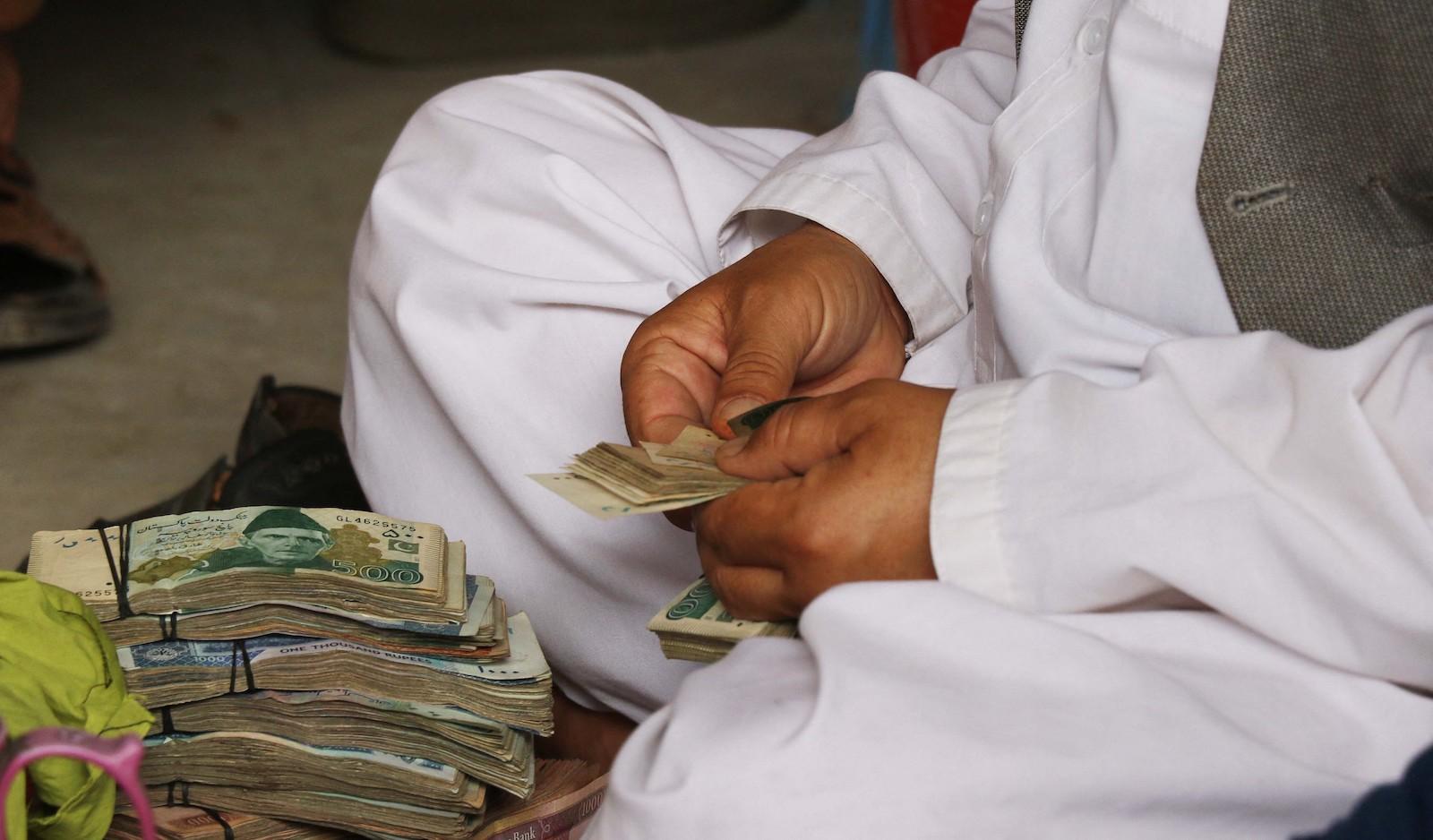 16 年 2021 月 XNUMX 日,阿富汗货币贬值导致交易商受到重创,导致阿富汗喀布尔的食品价格上涨,一名阿富汗货币兑换商正在数钱。照片:法新社通过 Anadolu Agency / Haroon Sabawoon