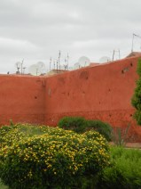 Red clay wall adorned with satellite dishes.