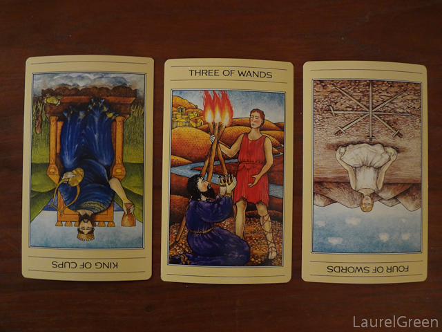 a three card taro spread with the king of cups reversed, the three of wands and the four of swords reversed