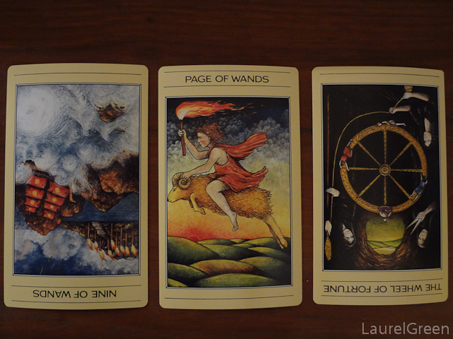 a three card tarot spread with the nine of wands reversed, the page of wands and the wheel of fortune reversed