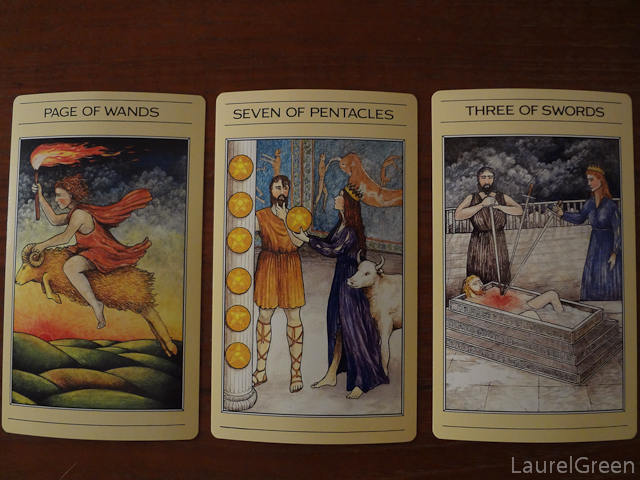a three card tarot spread with the age of wands, the seven of pentacles and the three of swords