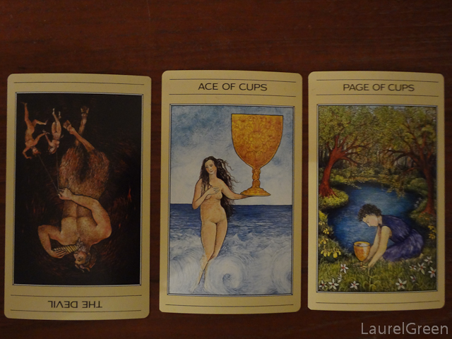 a three card tarot spread with the devil reversed, the ace of cups and the page of cups