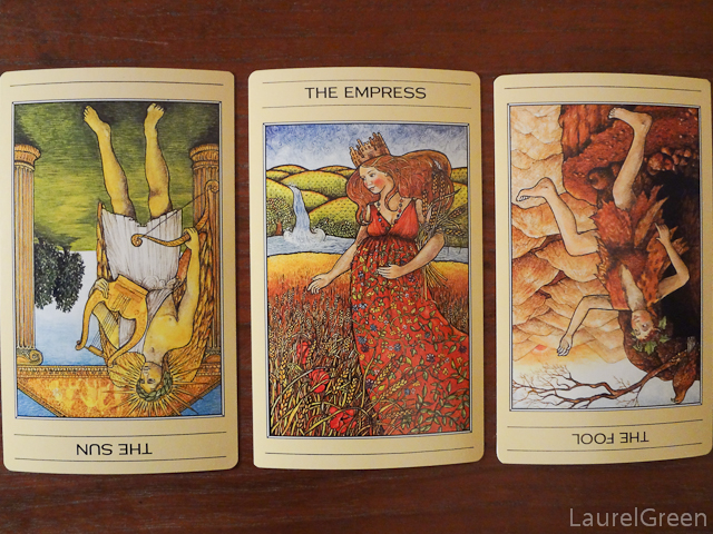 a three card tarot spread with the sun reversed, the empress and the fool reversed