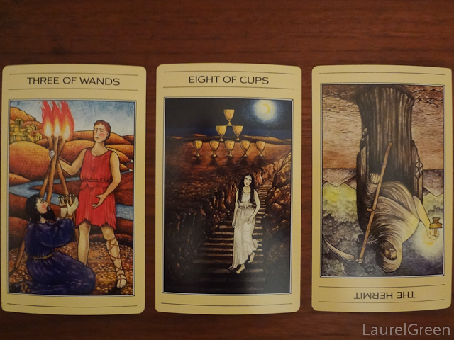a three card tarot spread with the three of wands, the eight of cups and the hermit reversed