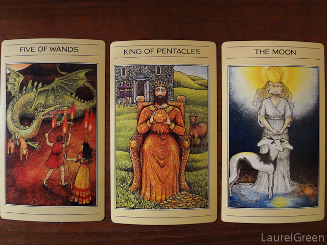 a three card tarot spread with the five of wands, the king of pentacles and the moon