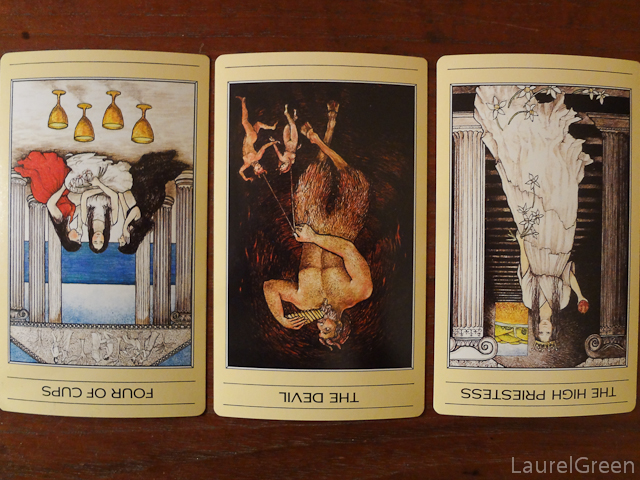 a three card tarot spread with the four of cups reversed, the devil reversed and the high priestess reversed