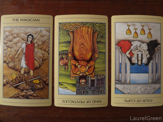a three card tarot spread with the magician, the king of pentacles reversed and the four of cups reversed