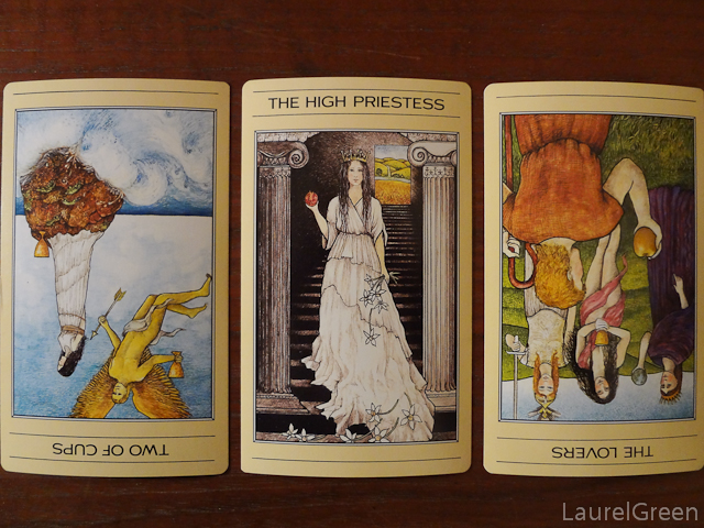 a three card tarot spread with the two of cups reversed, the high priestess and the lovers reversed