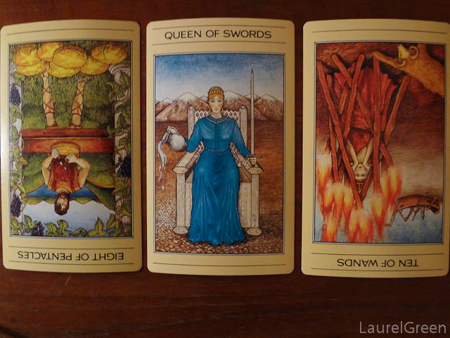 a three card tarot spread with the eight of pentacles reversed, the queen of swords and the ten of wands reversed