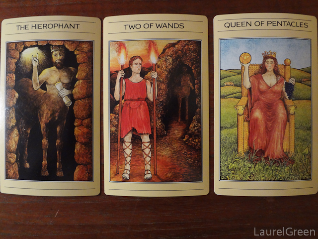 a three card tarot spread with the hierophant, the two of wands and the queen of pentacles