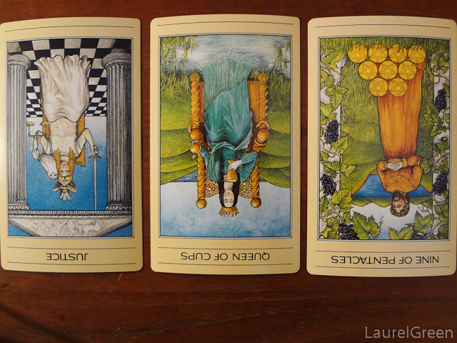 a three card tarot spread with justice reversed, the queen of cups reversed and the nine of pentacles reversed