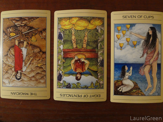 a three card tarot spread with the magician reversed, the eight of pentacles reversed and the seven of cups