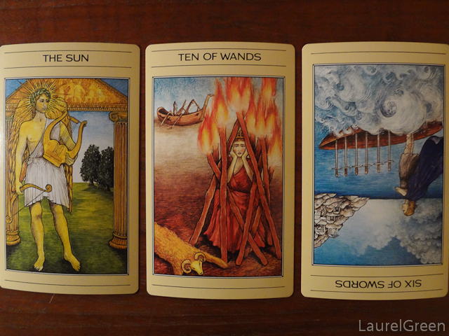 a three card tarot spread with the sun, the ten of wands and the six of swords reversed