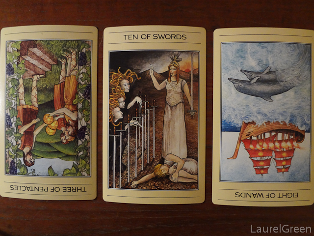 a three card tarot spread with the three of pentacles reversed, the ten of swords and the eight of wands reversed