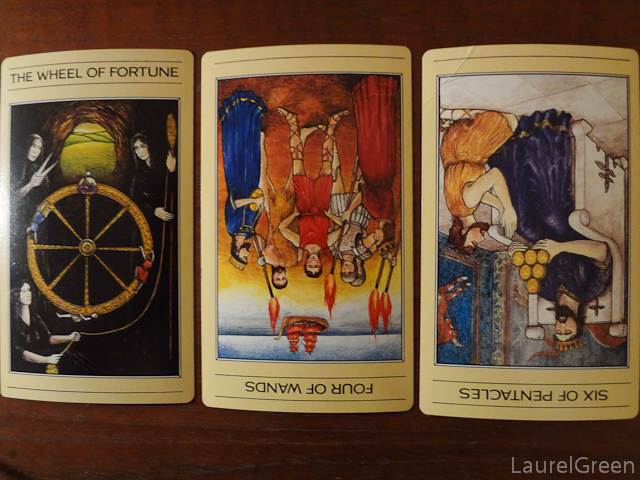 a three card tarot spread with the wheel of fortune, the four of wands reversed and the six of pentacles reversed