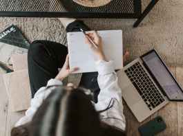 faceless lady with notebook and laptop on floor at home