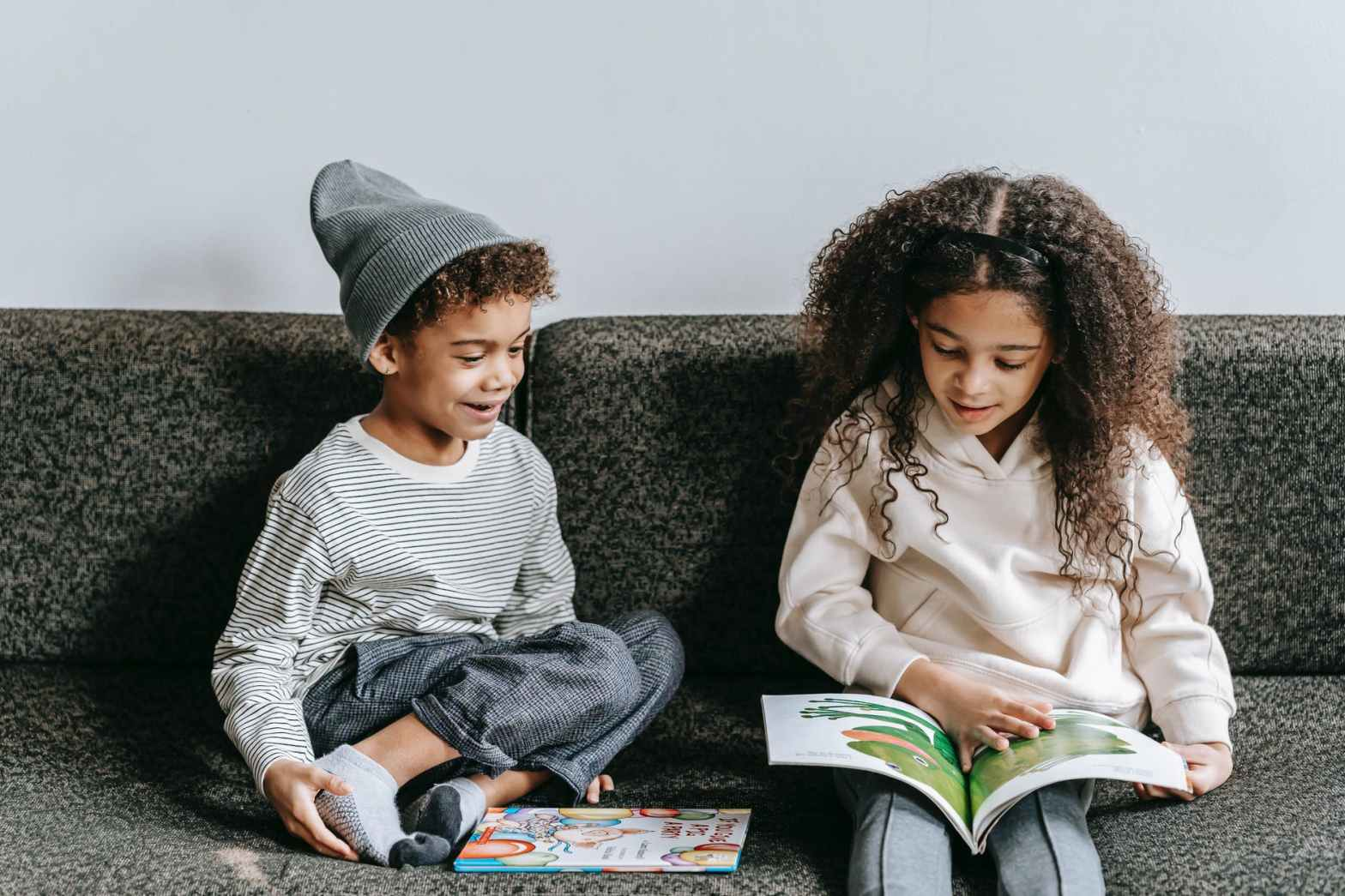delighted ethnic little siblings reading interesting book on couch