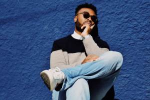 Young man of African origin in sunglasses , jumper and jeans with his knee on the other leg - wondering how to deal with snoring affecting his personal life.