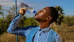 Avoid dangers of Dehydration -African man with low cut hair drinking water from a bottle