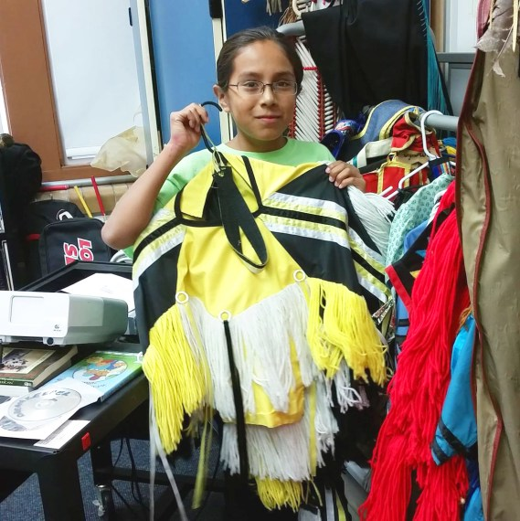 Santino Decory holds up regalia he wears at powwows. 'This one's my favorite,' he says. (Next Gen Radio/Angela Nguyen)