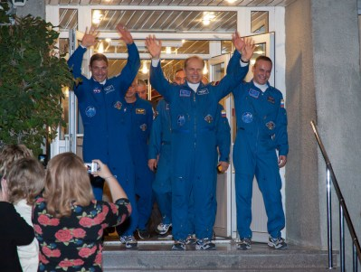 Expedition 37/38 crew members, Flight Engineer Michael Hopkins of NASA, left, Soyuz Commander Oleg Kotov of Roscosmos, and Russian Flight Engineer Sergey Ryazanskiy, right, wave farewell to family and friends as they depart the Cosmonaut Hotel to suit-up for their soyuz launch to the International Space Station on Wednesday, Wednesday, Sept. 25, 2013, in Baikonur, Kazakhstan. Launch of the Soyuz rocket will send Hopkins, Kotov and Ryazanskiy on a five-month mission aboard the International Space Station. Photo Credit: (NASA/Victor Zelentsov)