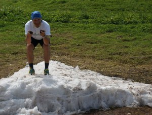 Mann in kurzer Hose geht auf Schneerest in Hocke