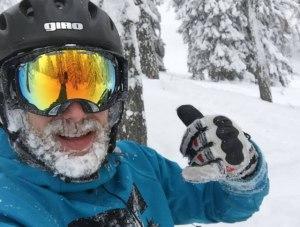 Schifahrer mit gefrorenem Bart haelt den Daumen hoch