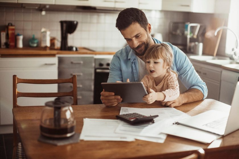 Photo of a father budgeting with daughter on lap
