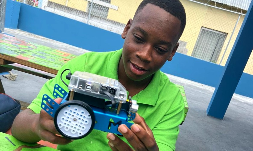 Photo of teenage Bahamian boy holding an mechanical toy