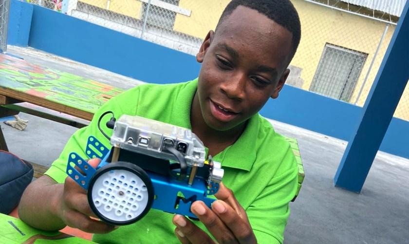 Photo of teenage Bahamian boy holding an mechanical toy