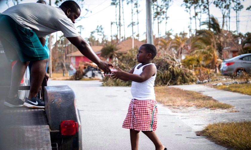 Photo of a man on truck giving an item to a Bahamian child